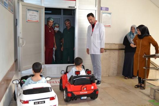 Çocuklar gülerek bindikleri akülü arabayla ameliyata giriyor