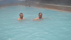 Kar yağışının altında havuzun keyfini çıkarıyorlar