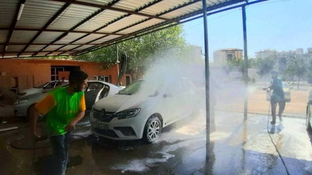 İşçiler sıcak havada tazyikli suyla serinliyor