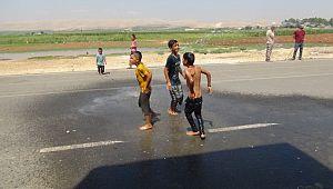 Anne çocuklarını hortumla su sıkarak serinletti ( Video Haber )